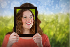 Composite image of woman holding digital tablet in front of her face. Woman holding digital tablet in front of her face against green meadow stock photo