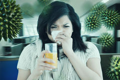 Composite image of woman holding a glass of orange juice while sneezing. Woman holding a glass of orange juice while sneezing against empty office with separate stock photos