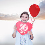 Composite image of woman holding heart card Royalty Free Stock Photos