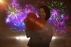 Composite image of woman holding heart shape paper Stock Photos