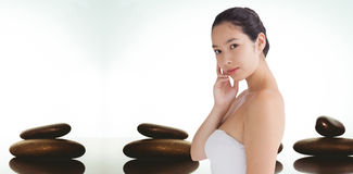Composite image of woman holding her chin. Woman holding her chin  against zen stones Stock Image