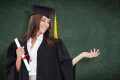Composite image of a woman holding her hand out with a degree in her other hand as she smiles Royalty Free Stock Image