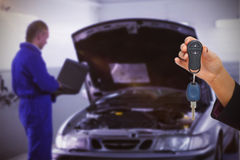 Composite image of woman holding key and small car Royalty Free Stock Image