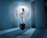 Composite image of woman holding laptop in light bulb Stock Photos