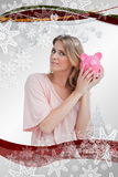 Composite image of woman holding a piggy bank up to her head Stock Photography
