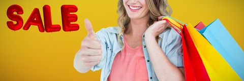 Composite image of woman holding some shopping bags. Woman holding some shopping bags against abstract mustard background royalty free stock photos