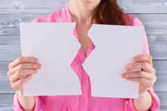 Composite image of woman holding torn sheet of paper Royalty Free Stock Images
