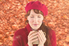 Composite image of woman holding a warm cup. Woman holding a warm cup against autumn leaves on the ground stock photography