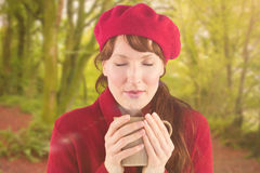 Composite image of woman holding a warm cup. Woman holding a warm cup against peaceful autumn scene in forest stock photography