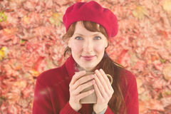 Composite image of woman holding a warm cup. Woman holding a warm cup against peaceful autumn scene in forest royalty free stock photography