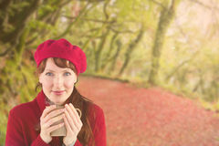 Composite image of woman holding a warm cup. Woman holding a warm cup against peaceful autumn scene in forest stock image