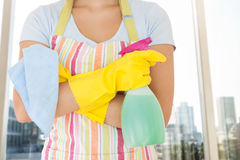 Composite image of woman holding window cleaner and rag Royalty Free Stock Photography