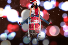 Composite image of woman jumping with shopping trolley. Woman jumping with shopping trolley against blurred lights Royalty Free Stock Photo