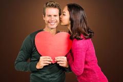 Composite image of woman kissing boyfriend with red heart shape. Woman kissing boyfriend with red heart shape  against shades of brown Stock Photos