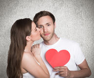 Composite image of woman kissing man as he holds heart Stock Images