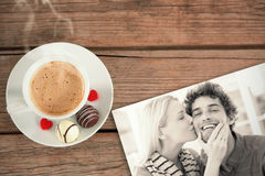 Composite image of woman kissing man on his cheek. Woman kissing man on his cheek against cup of coffee stock photography