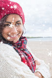 Composite image of woman in knitted hat and pullover smiling at beach Stock Photography