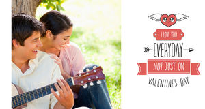 Composite image of woman laughing with her friend who is playing the guitar Stock Photos
