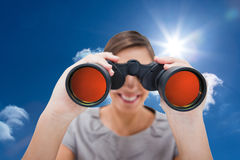 Composite image of woman looking through spyglasses Royalty Free Stock Image