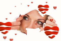 Composite image of woman looking through torn paper. Woman looking through torn paper against hearts stock photo