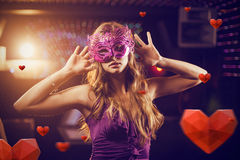 Composite image of woman with masquerade dancing on dance floor Stock Photo
