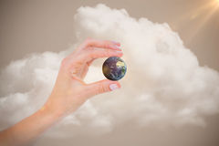Composite image of woman presenting little earth with her hand Stock Images