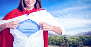 Composite image of woman pretending to be superhero. Woman pretending to be superhero against image of mountain landscape Stock Photo
