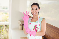 Composite image of woman putting on plastic gloves. Woman putting on plastic gloves against room full of shelves Stock Photo