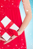 Composite image of woman in red dress holding gift Royalty Free Stock Image