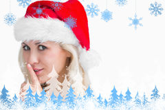 Composite image of woman in santa hat making silence gesture Stock Photo