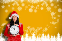 Composite image of woman shocked at the time. Woman shocked at the time against blurred fir tree background Stock Image