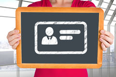 Composite image of woman showing chalkboard to camera Royalty Free Stock Photos