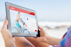 Composite image of woman sitting on beach in deck chair using tablet pc. Woman sitting on beach in deck chair using tablet pc against dating website Royalty Free Stock Image