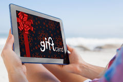 Composite image of woman sitting on beach in deck chair using tablet pc Royalty Free Stock Image