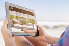 Composite image of woman sitting on beach in deck chair using tablet pc. Woman sitting on beach in deck chair using tablet pc against holidays booking app Royalty Free Stock Photography