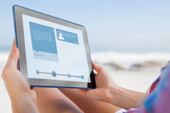 Composite image of woman sitting on beach in deck chair using tablet pc Royalty Free Stock Photo