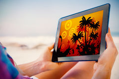 Composite image of woman sitting on beach in deck chair using tablet pc Royalty Free Stock Images
