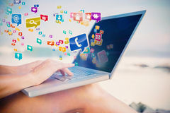 Composite image of woman sitting on beach using her laptop Stock Image