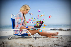Composite image of woman sitting on beach using her laptop 3d Royalty Free Stock Photography