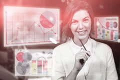 Composite image of woman smiling against colored graph. Graph against portrait of businesswoman holding pencil Stock Photos