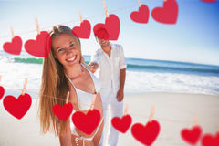 Composite image of woman smiling at camera with boyfriend holding her hand Stock Photos