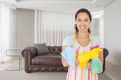 Composite image of woman standing with arms crossed holding cleaning products. Woman standing with arms crossed holding cleaning products against brown leather Royalty Free Stock Images