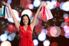Composite image of woman standing with shopping bags. Woman standing with shopping bags against blurred lights Stock Images