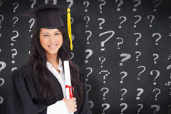Composite image of a woman standing to the side slightly with her degree and dressed in her graduati Royalty Free Stock Photo
