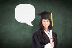 Composite image of a woman standing to the side slightly with her degree and dressed in her graduati Royalty Free Stock Photography