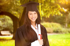 Composite image of a woman standing to the side slightly with her degree and dressed in her graduati Royalty Free Stock Photos