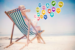 Composite image of woman in sunhat sitting on beach in deck chair using tablet pc Stock Photography