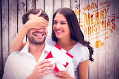Composite image of woman surprising boyfriend with gift Stock Images