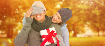 Composite image of woman surprising husband with gift stock photo