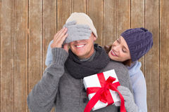 Composite image of woman surprising husband with gift Royalty Free Stock Images